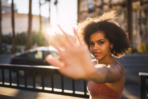 USA, Nevada, Las Vegas, portrait of young woman in the city in backlight raising her hand - KKAF02895