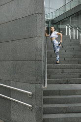 Young woman doing stretching exercise on stairs - FMGF00078