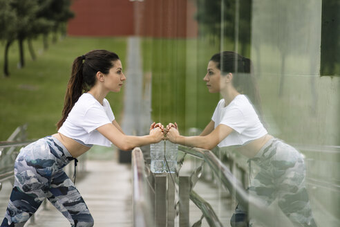 Young woman doing stretching exercise reflected in glass facade - FMGF00084