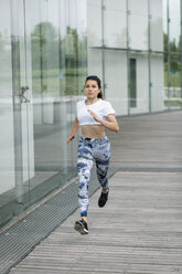 Young woman running along building in the city - FMGF00087