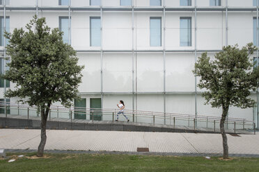 Young woman running along building in the city - FMGF00093