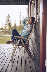 Sweden, Lapland, portrait of young woman sitting on chair on veranda relaxing - RSGF00025