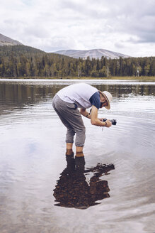 Sweden, Lapland, man standing in water taking photos - RSGF00031