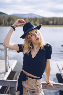 Sweden, Lapland, portrait of fashionable blond woman wearing black hat standing on jetty - RSGF00037