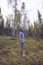 Sweden, Lapland, man standing on forest glade relaxing - RSGF00040