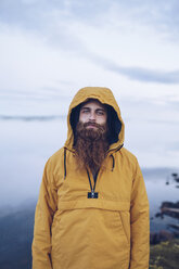 Sweden, Lapland, portrait of young man with full beard wearing yellow windbreaker in nature - RSGF00043