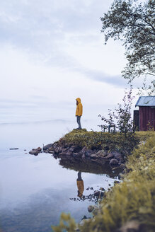 Sweden, Lapland, man wearing  windbreaker standing at water's edge looking at distance - RSGF00046