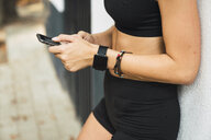 Fit young woman with a smartwatch, using smartphone - KKAF02951