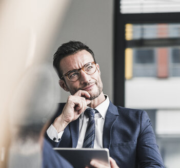 Businessman using digital tablet, sitting in office with feet up - UUF15779