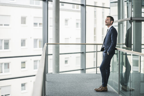 Successful businessman standing in office building, looking out of window, daydreaming - UUF15794