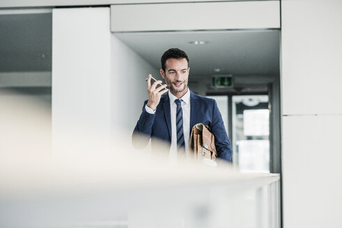Businessman with briefcase walking in office building, using smartphone - UUF15797