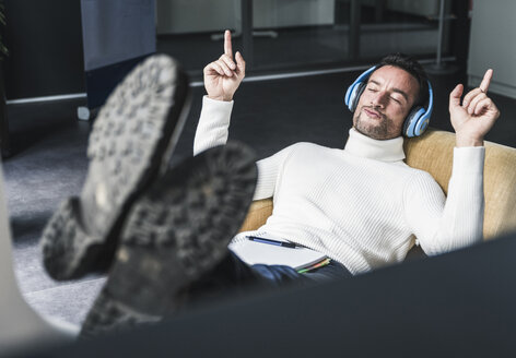 Businessman listening relaxed music in his office - UUF15836