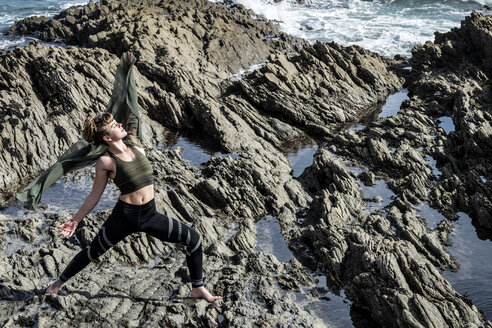 Young woman with brown hair and dreadlocks wearing sportswear standing on rocky shore by ocean, doing Tai Chi. - MINF09162