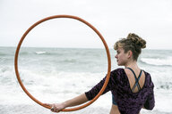 Young woman with brown hair and dreadlocks standing on a sandy beach by the ocean, balancing hula hoop. - MINF09165