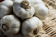 High angle view of a few garlic bulbs in a basket. - MINF09495