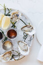 Platter of oysters on ice with lemons and sauces - MINF09513