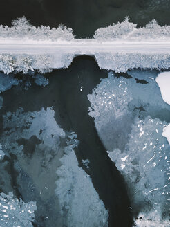 High angle distant view of person paddleboarding in lake by bridge during winter - CAVF53207