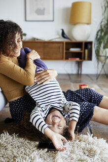 Happy mother holding daughter upside down while sitting on floor at home - CAVF53219