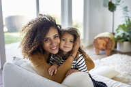Portrait of mother embracing daughter while sitting on sofa at home - CAVF53222