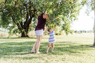 Mother with daughter picking apples from tree while standing on grassy field - CAVF53273