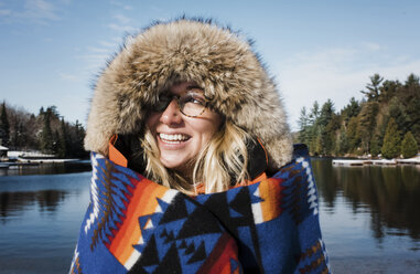 Cheerful woman wearing fur coat while being wrapped in blanket against lake at Algonquin Provincial Park - CAVF53285