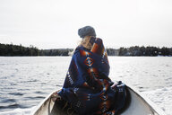 Rear view of woman with blanket sitting in boat on lake at Algonquin Provincial Park during winter - CAVF53288