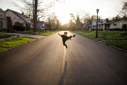 Full length of playful boy kicking in air while practicing karate on road during sunset - CAVF53294