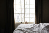 Portrait of girl hiding behind bed at home - CAVF53345