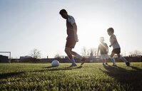Low angle view of man playing soccer with children on grassy field against clear sky during sunset - CAVF53357