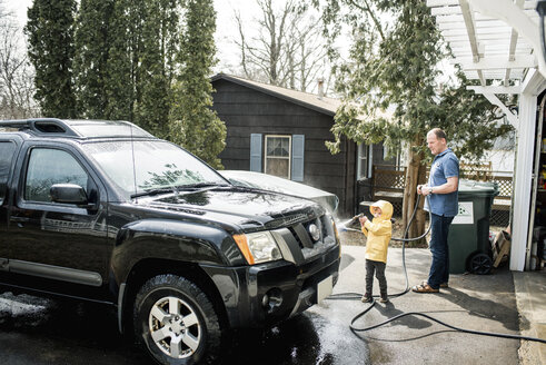 Grandson with grandfather cleaning sports utility vehicle at yard - CAVF53366