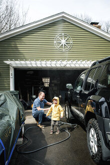 Grandson screaming while grandfather cleaning sports utility vehicle at garage - CAVF53369