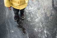 Low section of boy in raincoat standing on wet road - CAVF53372
