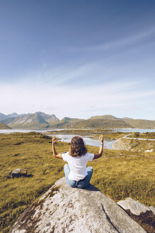 Norway, Lofoten, back view of young woman sitting on a rock doing yoga - RSGF00056