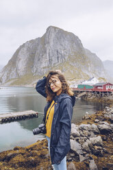 Norway, Lofoten, Hamnoy, portrait of young woman with camera - RSGF00068