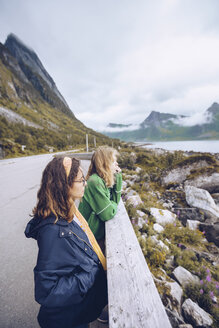 Norway, Senja, two young woman standing at the roadside looking at view - RSGF00074