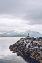 Norway, Senja, man standing on rock at the coast - RSGF00077