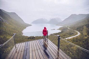 Norway, Senja, rear view of man standing on an observation deck at the coast - RSGF00083