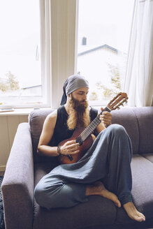 Bearded man playing guitar on couch - RSGF00086