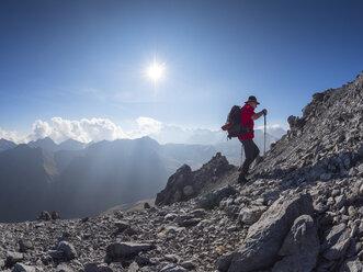 Border region Italy Switzerland, senior man hiking in mountain landscape at Piz Umbrail - LAF02146