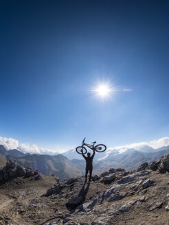 Border region Italy Switzerland, cheering man with mountainbike on peak of Piz Umbrail - LAF02152