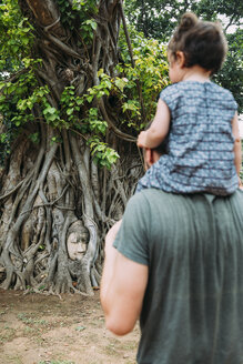 Thailand, Ayutthaya, Father and daughter visiting the Buddha head in between tree roots at Wat Mahathat - GEMF02467