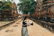 Thailand, Ayutthaya, Mother and daughter playing in the ancient ruins of a temple at Wat Mahathat - GEMF02479