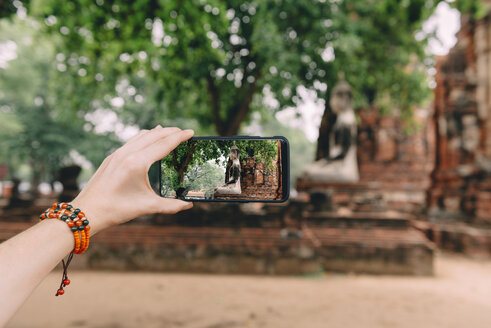 Thailand, Ayutthaya, Woman taking a photo of a Buddha statue at Wat Mahathat - GEMF02482