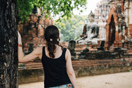 Thailand, Ayutthaya, Woman looking at a Buddha statue at Wat Mahathat - GEMF02485