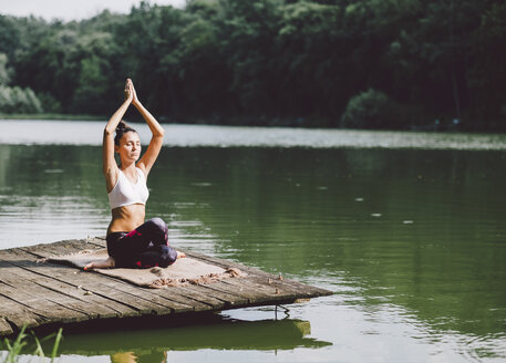 Woman with arms raised meditating while sitting on pier over lake in forest - CAVF53405