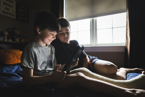 Smiling boy with broken leg using tablet computer while sitting by brother on bed at home - CAVF53411