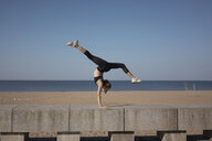 Full length of flexible young woman with legs apart practicing handstand on promenade by sea against sky during sunny day - CAVF53429