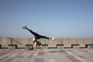 Full length of flexible young woman with legs apart practicing handstand on promenade against sky during sunny day - CAVF53432