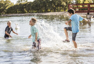 Happy friends splashing water in lake - CAVF53450
