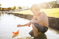 Shirtless boy playing with paper boat while crouching in lake - CAVF53456